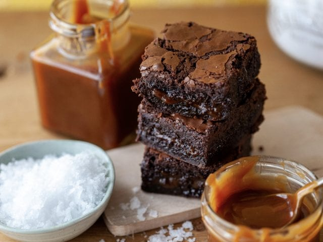 a tower of brownies surrounded by caramel sauce and salt
