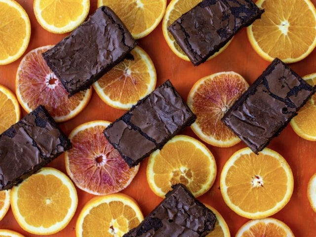 A selection of rolly's brownies on a bed of oranges