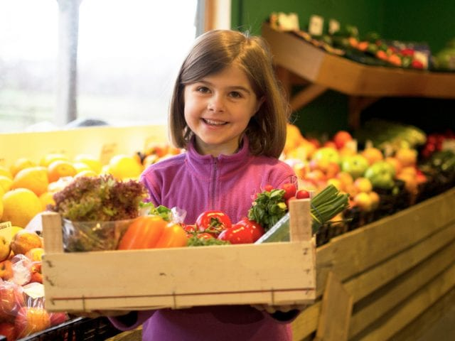 small girl holding a crate of vegetables