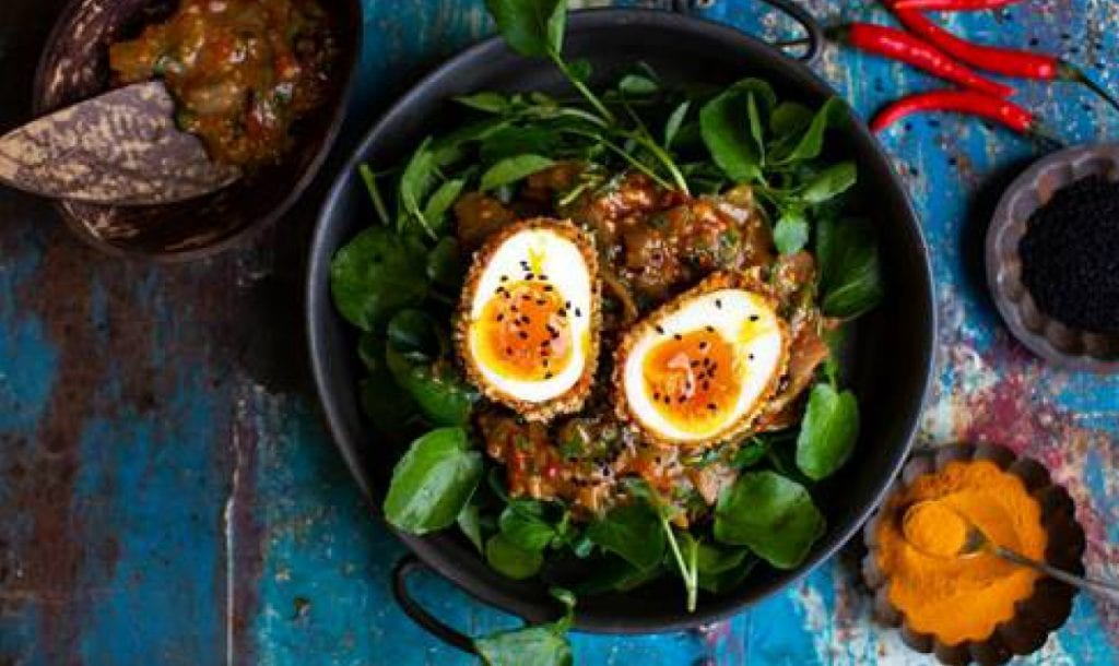a bowl of salad with watercress and eggs
