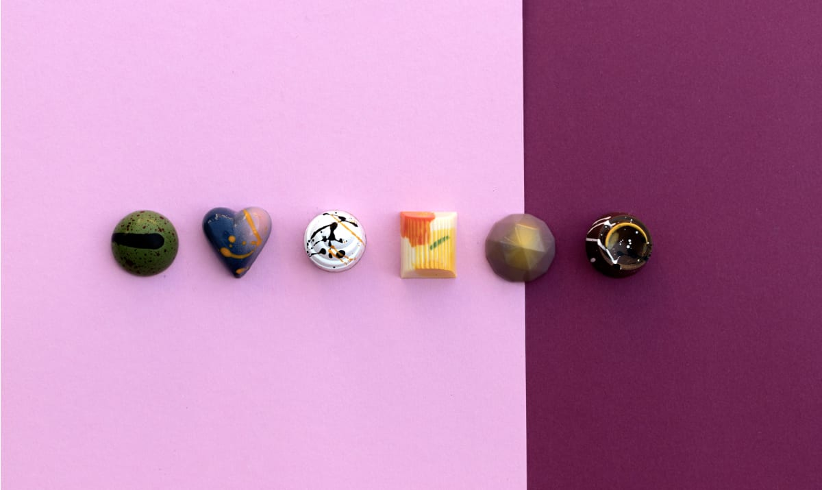 a selection of chocolate arthouse chocolates on a pink background